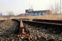Stillgelegtes und abgetrenntes Bahngleis der Hamburger Hafenbahn - verlassenes Bahngebäude und Zollzaun an der Versmannstrasse am Baakenhafen.