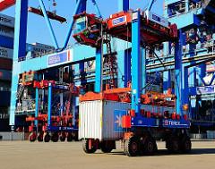 Einer der vielen Portalhubwagen auf dem Gelände des Terminals Burchardkai transportiert seine Ladung zum Containerlager - der Fahrzeugführer sitzt hoch oben in der Kanzel des Transportfahrzeugs.