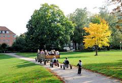 Kinderausflug im Eppendorfer Park - ein Trecker zieht einen Anhänger, der mit Kindergartenkindern besetzt ist - einige folgen mit einem Tretauto und Roller. Fotos aus dem Stadtteil Hamburg Eppendorf.