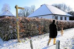 Alsterwanderweg im Winter - Holzschild mit Inschrift und Zeichen Pilgerweg.