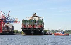 Der hochbeladene Containerfrachter HATTA wird mit Hilfe der Schlepper an seinen Liegeplatz im Hafen Hamburgs bewegt.