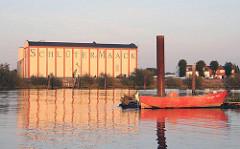 Blick über den Holzhafen - Rotes Boot am Holzsteg - Getreidespeicher hinter dem Moorfleeter Deich.