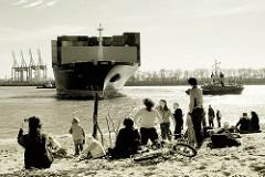 Der Frachter CMA CGM CARMEN läuft in den Hamburger Hafen ein - das Containerschiff wendet auf der Elbe; Zuschauer am Elbstrand bei der Strandperle in Hamburg Othmarschen.