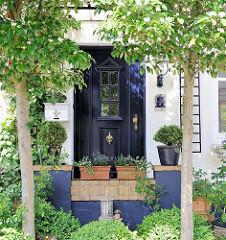 Hauseingang eines historischen Wohngebäudes im Hamburger Stadtteil Blankenese - Grünpflanzen und Bäume im Vorgarten des Hauses.