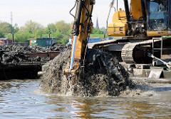 Baggerschaufel mit Schlamm wird aus dem Spreehafen in Hamburg Wilhelmsburg / Kleiner Grasbrook herausgeholt - Baggerarbeiten im Hamburger Hafen.