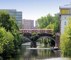 Bahnbrücke und S-Bahnzug über dem Mittelkanal in Hamburg Hammerbrook - im Hintergrund Bürohäuser der City Süd.