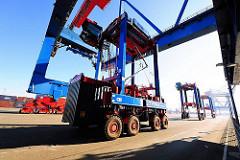 Der Portalhubwagen nimmt den Container auf - weitere Transportfahrzeuge warten im Hintergrund auf ihre Ladung.