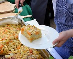 Biohof Gut Wulksfelde - Bauernmarkt. Aussteller präsentieren ihre Bioprodukte und Kunsthandwerk. Ein Stück Quiche wird auf einem Teller gelegt.