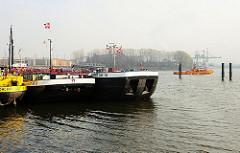 Binnenschiffe liegen im Finkenwerder Vorhafen - eine Barkasse fährt im Hintergrund Richtung Saugerstation in Hamburg Finkenwerder.