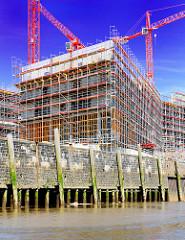Ebbe am Versmannkai des Baakenhafens - die Holzständer der Kaianlage sind freigelegt - Baustelle mit Baukränen der HafenCity Universität Hamburg HCU