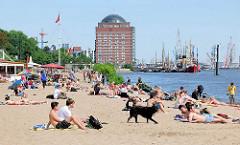 Strandszene in Hamburg Othmarschen - Menschen liegen im Sand in der Sonne am Ufer der Elbe - im Hintergrund das ehem. Kühlhaus von Neumühlen und der Museumshafen mit historischen Schiffen.