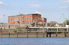 Industriegebäude mit Ziegelfassade - Rohre im Reiherstieghafen; Motive aus Hamburg Wilhelmsburg.