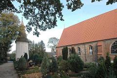 Kirche St. Johannis zu Neuengamme - vom Kirchenschiff getrennter Kirchturm - Grabsteine auf dem Kirchhof.