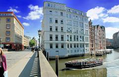 Blick von der Holzbrücke in der Hamburger Altstadt auf das Nikolaifleet; ein Barkasse mit Fahrgästen fährt unter die Brücke - hohe Kontorhäuser und Lagerhäuser am Fleetufer.