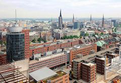 Blick über die Bürogebäude der Hamburger Hafencity / Speicherstadt am Kehrwieder - im Hintergrund Türme der Kirchen der Hansestadt Hamburg.