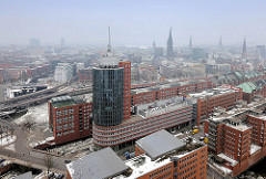 Hamburger Stadtteil Hafencity - moderne Neubauten, Büroturm - historische Speichergebäude; im Hintergrund die Kirchtürme der Hansestadt Hamburg.