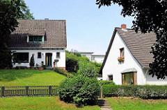Einzelhäuser mit weisser Fassade und Spitzdach in Hügellandschaft - Hausbau am Berg; Bilder aus Hamburg Eißendorf.