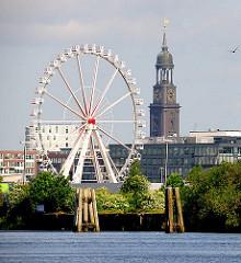 Blick über den Moldauhafen zum Riesenrad in der Hamburg Hafencity - rechts der Michel, die St. Michaeliskirche, dem Wahrzeichen Hamburgs.