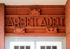ARBEIT ADELT - Inschrift über dem Eingang eines Wohnhauses in Hamburg Barmbek Süd.