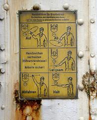 Schild am Kran an der Grossen Elbstrasse - Handzeichen im Kranbetrieb, Die Kranführer sind angewiesen nach diesen nur von einer Person zu gebenden Handzeichen zu fahren.