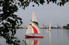 Alsterufer bei der Bellvue - Segelboote auf der Aussenalster - Hamburg Panorama mit Kirchtürmen im Hintergrund.