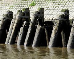 Streichdalben aus Holz schützen eine Kaimauer im Hamburger Hafen.