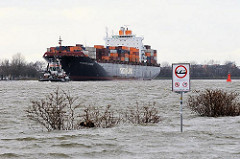Das Elbufer bei Hamburg Othmarschen steht nach einer Sturmflutwarnung unter Wasser - auf der Elbe ein Containerfrachter auf den Weg in den Hafen Hamburgs.