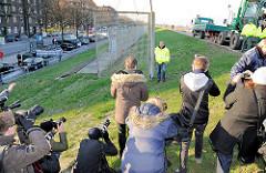 PressefotografInnen halten den historischen Moment des symbolischen Abrisses des Zollzauns durch den Hamburger Bürgermeister Olaf Scholz mit ihrer Kamera fest.