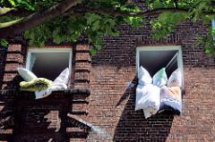 Sonniger Morgen in Hamburg Wilhelmsburg - Betten werden zum Lüften aus den Fenstern des Klinkergebäudes gehängt.