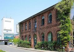 Mit grünen Rankpflanzen bewachsenes Backsteingebäude - Remise auf dem Bahrenpark, dem ehem. Gaswerk Hamburg Bahrenfeld.