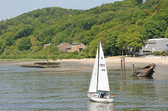 Ufer der Elbe bei Hamburg Blankenese  - Segelboot, zwei Schiffswracks - im Hintergrund Maschinenhaus der historischen Altoner Wasserwerke.