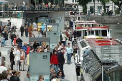 Blick auf den Schiffsanleger Jungfernstieg - Schiffe der weissen Flotte liegen an der Kaimauer - Hamburg Touristen warten auf eine Fahrt mit einem Alsterschiff.