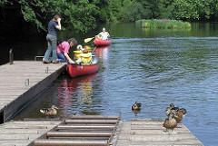 Kanus legen am Steg bei der Poppenbüttler Schleuse an - Enten sitzen in der Sonne.