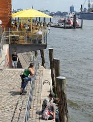Sonne am Wasser - Blick auf die Elbe an der Grossen Elbstrasse - Restaurant mit Terrasse am Wasser - eine Hafenfähre liegt am Ponton Altona Fischmarkt.