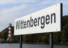 Schild am Anleger Wittenbergen - Leuchtturm im Hintergrund.