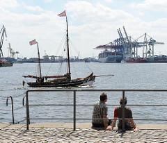 Blick von der Grossen Elbstrasse auf den Hamburger Hafen - ein Pärchen sitze auf der Kaimauer am Wasser des Hamburger Flusses, ein historisches Segelschiff fährt stromabwärts. Im Hintergrund die Terminalanlagen von Tollerort.