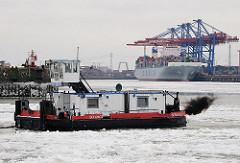 Schubschiff im Eis der Elbe im Hamburger Hafen - dunkle Abgaswolke - Dieselmotor; im Hintergrund das Terminal Tollerort.