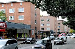 Autoverkehr in der Strassburger Strasse - Wohnblocks und Geschäfte in Hamburg Dulsberg.