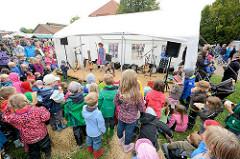 Kartoffelmarkt auf dem Biohof Wulkfelde - Theaterzelt; Kinder stehen dichtgedrängt und sehen der Vorstellung zu.