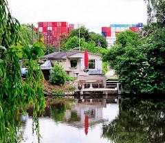 Schrebergartenlaube am Ufer des Assmannkanals - Containerstapel im Hintergrund in Hamburg Wilhelmsburg.