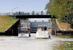Sportboote, Motorboote fahren in die Tatenberger Schleuse ein - Fahrradfahrer auf der Strasse über der Schleusenkammer.
