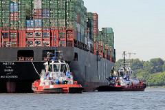 Hafenschlepper bei der Arbeit im Hamburger Hafen - die Schlepper wenden das Frachtschiff vor dem Waltershofer Hafen und bringen es an seinen Liegeplatz am Containerterminal EUROGATE.