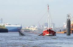 Ein Fischkutter fischt auf der Norderelbe kurz vor den Elbbrücken - im Hintergrund verlässt ein RoRo Frachtschiff den Hansahafen und fährt in die Elbe ein.