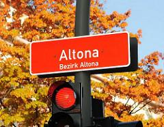 Schild, Altona - Bezirk Altona; weisse Schrift auf rotem Grund. Rote Ampel, Herbstlaub. Bilder aus Hamburg Altona.