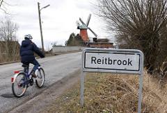 Stadtteilschild Reitbrook - Fahrrad auf der Strasse - Mühle von Hambug Reitbrook im Hintergrund.