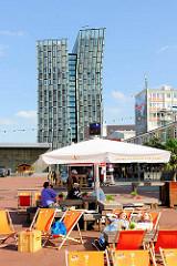 Beachclubfeeling auf dem Millerntorplatz - Liegestühle und Sonnenschirme in der Sonne - im Hintergrund das Hochhaus Tanzende Türme. Fotografien aus dem Hamburger Stadtteil St. Pauli.