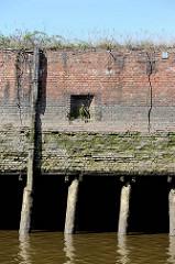 Alte Kaimauer im Hamburger Hafen; eingelassener Eisenringe zum Vertäuen von Schiffen; verwitterter Streichdalben. Bei Niedrigwasser zeigen sich die Baumstämme, die das Fundament der Kaianlage bilden.