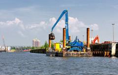 Ein Kran baggert von einem Ponton aus den Baakenhafen aus. Motive aus dem Hamburger Stadtteil Hafencity.