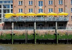 Aussengastronomie eines Restaurant an der Elbe im Altonaer Hafen - die Gäste sitzen auf einer Terrasse eines alten Speichergebäudes an der Elbe.
