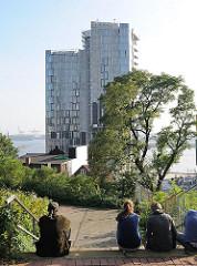 Blick vom Elbberg zum Neubau-Hochhaus am Elbufer bei der Großen Elbstrasse, Hamburg Altona Altstadt. Menschen sitzen in der Sonne auf der Treppe.